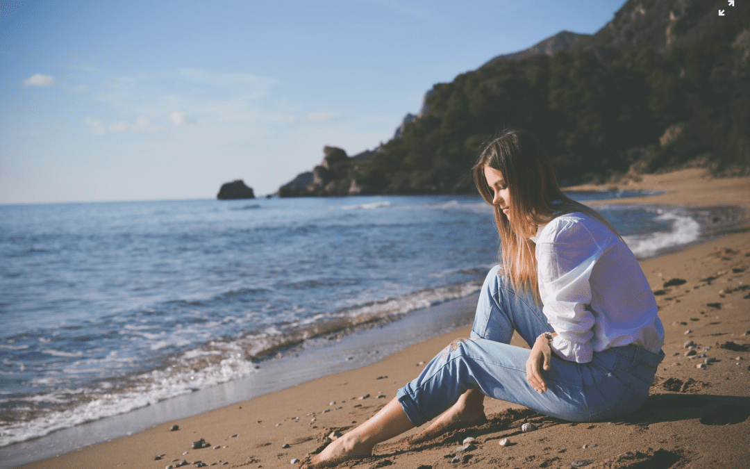 Woman sitting at beach with stomach pain